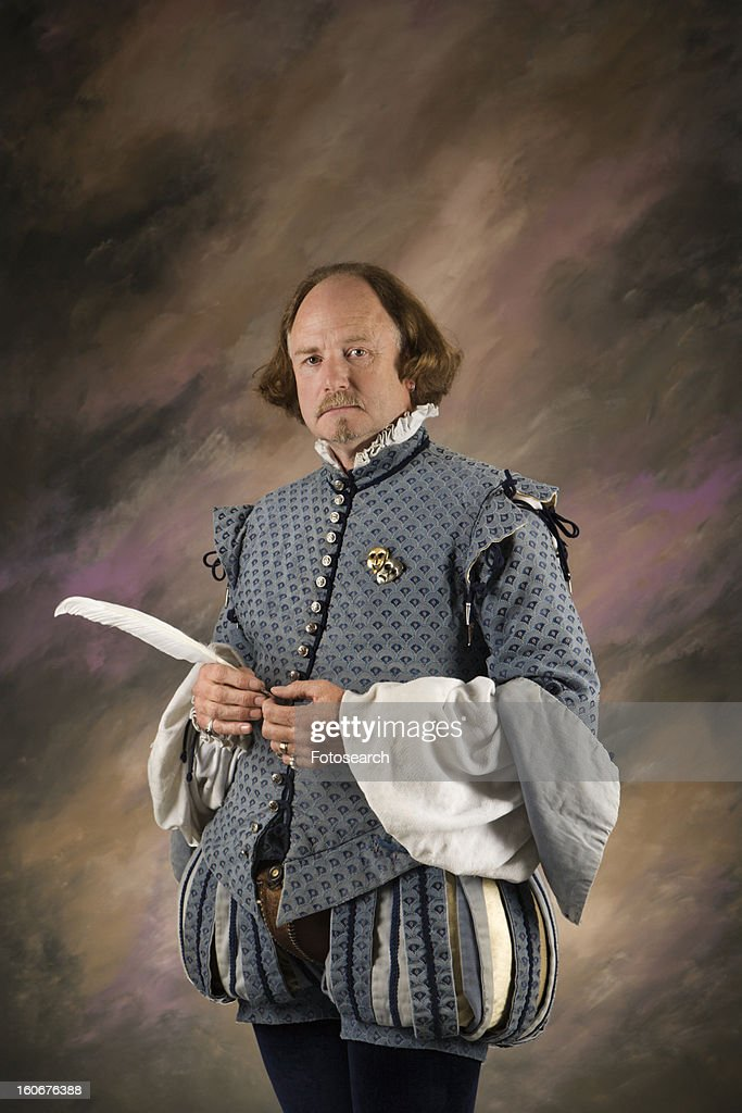 William Shakespeare in period clothing holding feather pen standing