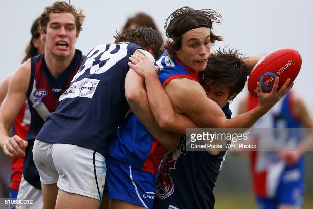 William Stephenson of the Power handpasses the ball under pressure during the round 12 TAC Cup match between Gippsland and Sandringham at Casey...