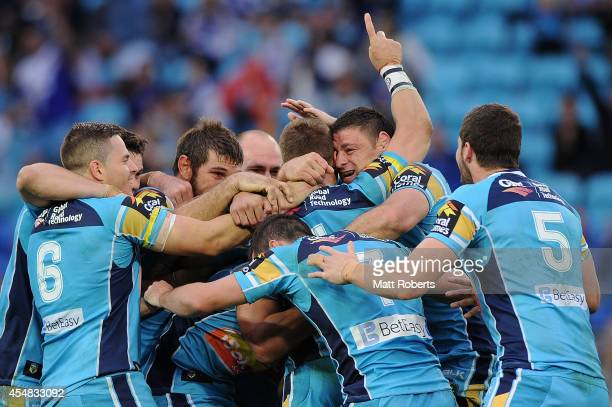 William Zillman of the Titans celebrates with team mates after kicking the winning field goal in extra time during the round 26 NRL match between the...