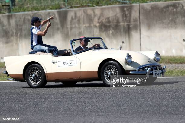 Williams' Brazilian driver Felipe Massa rides in a classic car during the drivers' parade before the Formula One Japanese Grand Prix in Suzuka on...