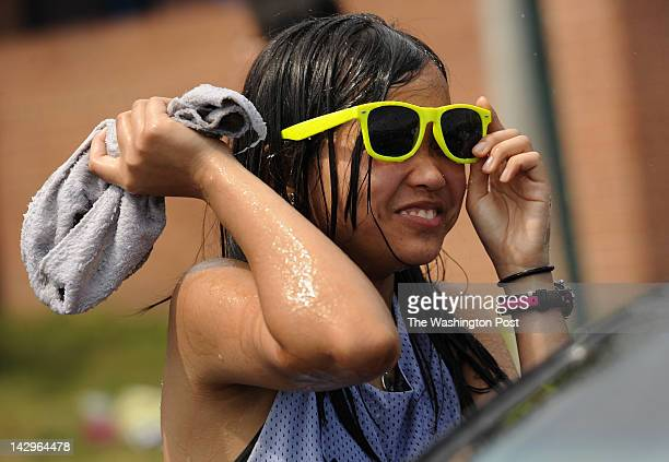 C Williams freshman Kathrina Policarpio gets ready to throw her wet towel at a teammate after getting sprayed with the hose while washing cars as a...