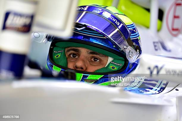 Williams Martini Racing's Brazilian driver Felipe Massa looks at a control screen in the pits during the first practice session at the Yas Marina...