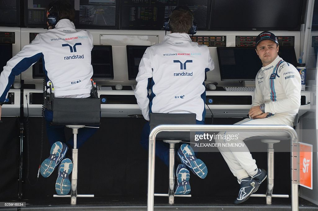 Williams Martini Racing's Brazilian driver Felipe Massa (R) sits in the pits during the first practice session of the Formula One Russian Grand Prix at the Sochi Autodrom circuit on April 29, 2016. / AFP / ALEXANDER