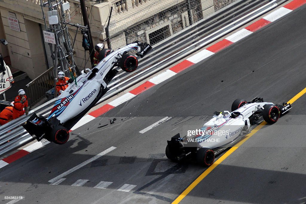 Williams Martini Racing's Finnish driver Valtteri Bottas drives next to Williams Martini Racing's Brazilian driver Felipe Massa crashed car during the first practice session at the Monaco street circuit, on May 26, 2016 in Monaco, three days ahead of the Monaco Formula 1 Grand Prix. / AFP / Valery HACHE