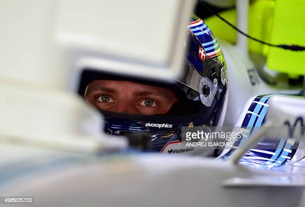 Williams Martini Racing's Finnish driver Valtteri Bottas looks at a control screen in the pits during the first practice session at the Yas Marina...