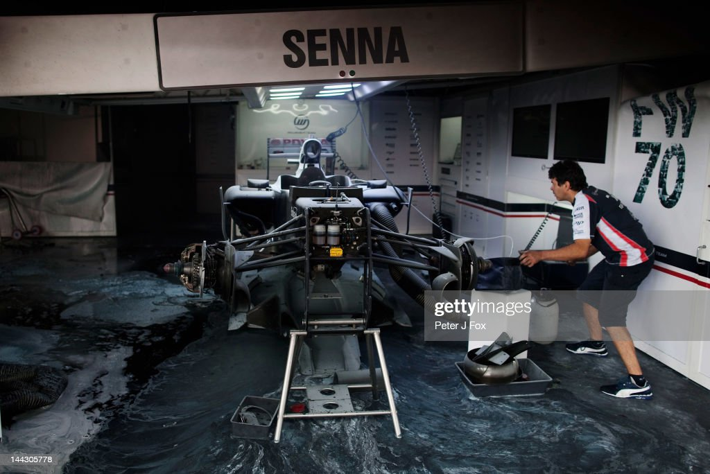 A Williams mechanic helps fight the fire that broke out at the back of their team garage after they celebrated winning the Spanish Formula One Grand Prix at the Circuit de Catalunya on May 13, 2012 in Barcelona, Spain.