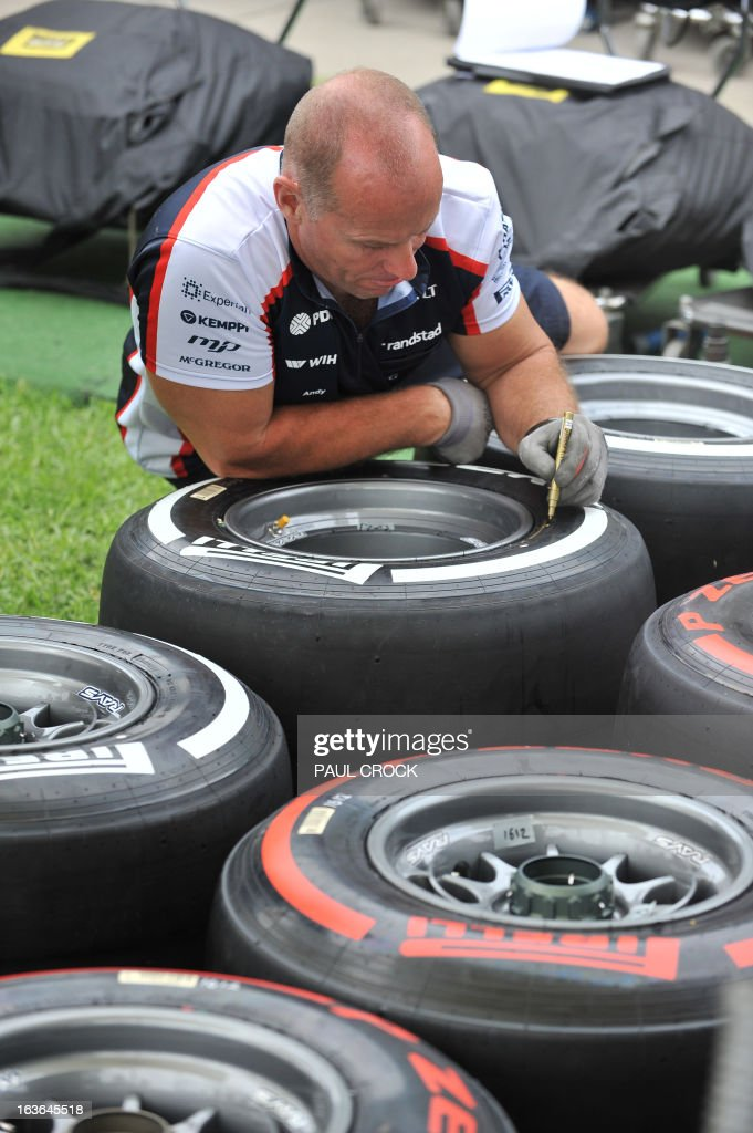 A Williams mechanic marks up tyre sets during set-up for the Formula One Australian Grand Prix in Melbourne on March 14, 2013. Reigning World Champion Red Bull Driver Sebastien Vettel of Germany was critical of the new season tyres in pre-season practice. IMAGE STRICTLY TO EDITORIAL USE - STRICTLY NO COMMERCIAL USE AFP PHOTO / Paul CROCK