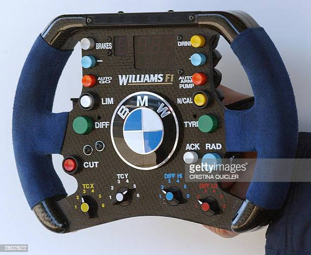 Williams mechanic shows the Chinese HoPin Tung's wheel during a training session in the pits at Jerez race ring 11 December 2003 AFP PHOTO Cristina...