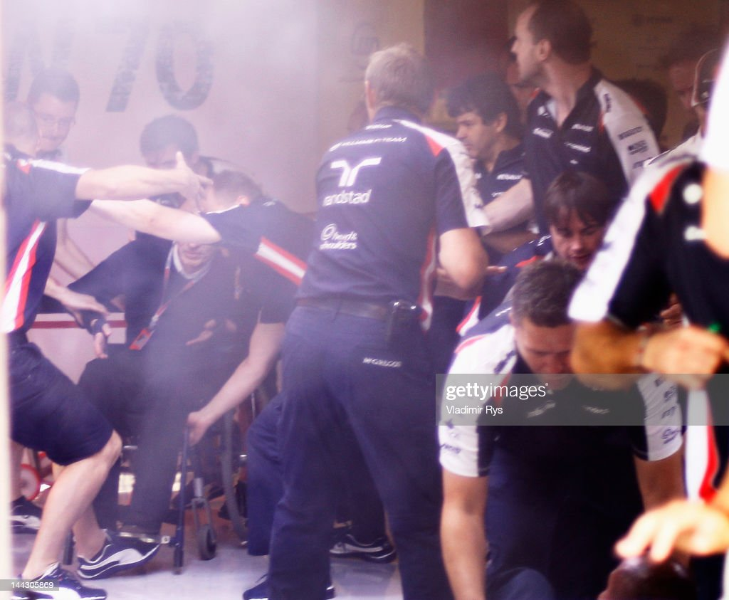 Williams mechanics help Sir Frank Williams to safety as a fire breaks out at the back of their team garage after they celebrated winning the Spanish Formula One Grand Prix at the Circuit de Catalunya on May 13, 2012 in Barcelona, Spain.