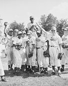 Rudy Davis of Hackensack is lifted into the air by teammates after pitching the Jersey team to a 20 victory over California in the consolation game...