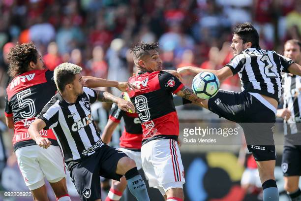 Willian Arao and Paolo Guerrero of Flamengo struggle for the ball with Victor Luis and Igor Rabello of Botafogo during a match between Flamengo and...