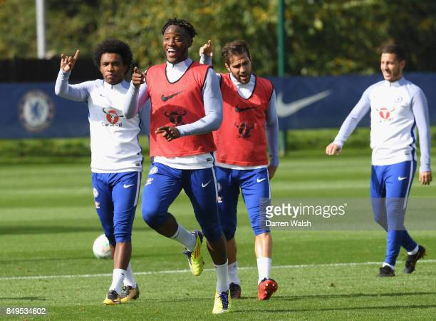 Willian Cesc Fabregas and Michy Batshuayi of Chelsea share a joke during a training session at Chelsea Training Ground on September 19 2017 in Cobham...