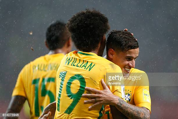 Willian of Brazil celebrates with teammate Philippe Coutinho after scoring the second goal of his team during a match between Venezuela and Brazil as...