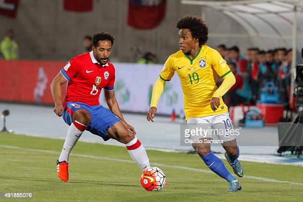 Willian of Brazil drives the ball as Jean Beausejour of Chile defends during a match between Chile and Brazil as part of FIFA 2018 World Cup...