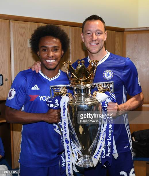Willian of Chelsea and John Terry of Chelsea pose with the Premier League Trophy in the changing room after the Premier League match between Chelsea...