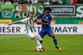 Willian of Chelsea competes for the ball with Philipp Schobesberger of Rapid Vienna during an friendly match between SK Rapid Vienna and Chelsea FC...