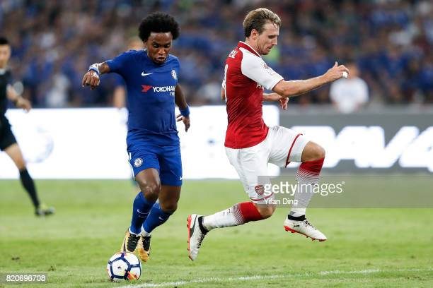 Willian of Chelsea dribbles past Nacho Monreal of Arsenal during the PreSeason Friendly match between Arsenal FC and Chelsea FC at Birds Nest on July...