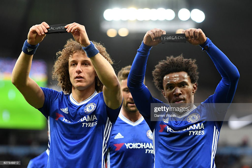 Willian (R) of Chelsea holds up the black armband to commemorate the victims of the plane crash involving the Brazilian club Chapecoense along with his team mate David Luiz after scoring his team's second goal during the Premier League match between Manchester City and Chelsea at Etihad Stadium on December 3, 2016 in Manchester, England.