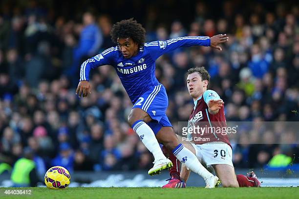 Willian of Chelsea is tackled by Ashley Barnes of Burnley during the Barclays Premier League match between Chelsea and Burnley at Stamford Bridge on...