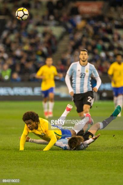 Willian Silva of the Brazilian National Football Team falls after a contest with Nicolas Tagliafico of the Argentinan National Football Team during...