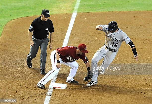 Willie Bloomquist of the Arizona Diamondbacks tags out Josh Rutledge of the Colorado Rockies as third base umpire Mark Wegner looks on at Chase Field...