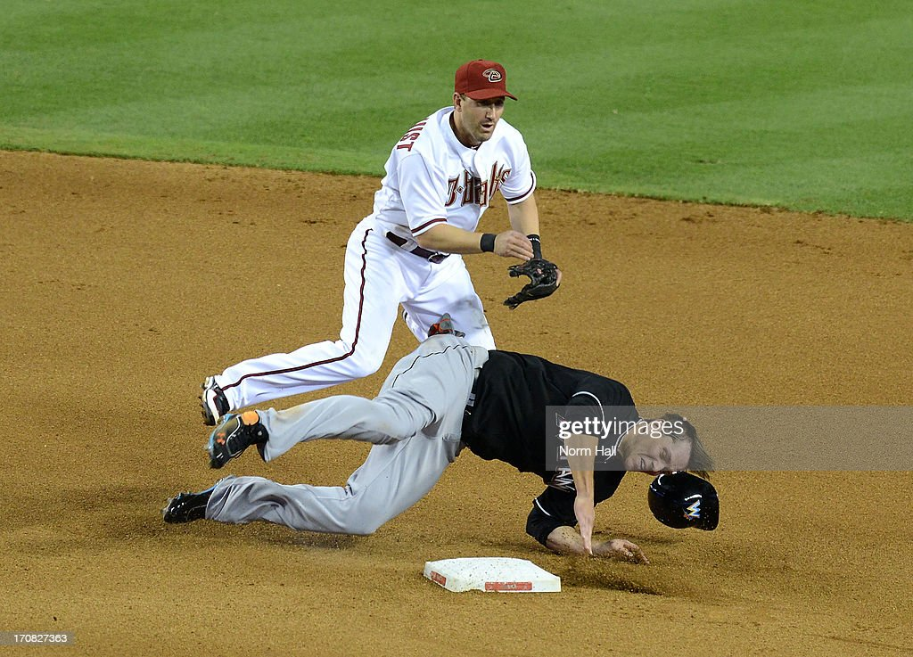 Willie Bloomquist #18 of the Arizona Diamondbacks turns a double play as Logan Morrison #5 of the Miami Marlins slides into second base at Chase Field on June 18, 2013 in Phoenix, Arizona.