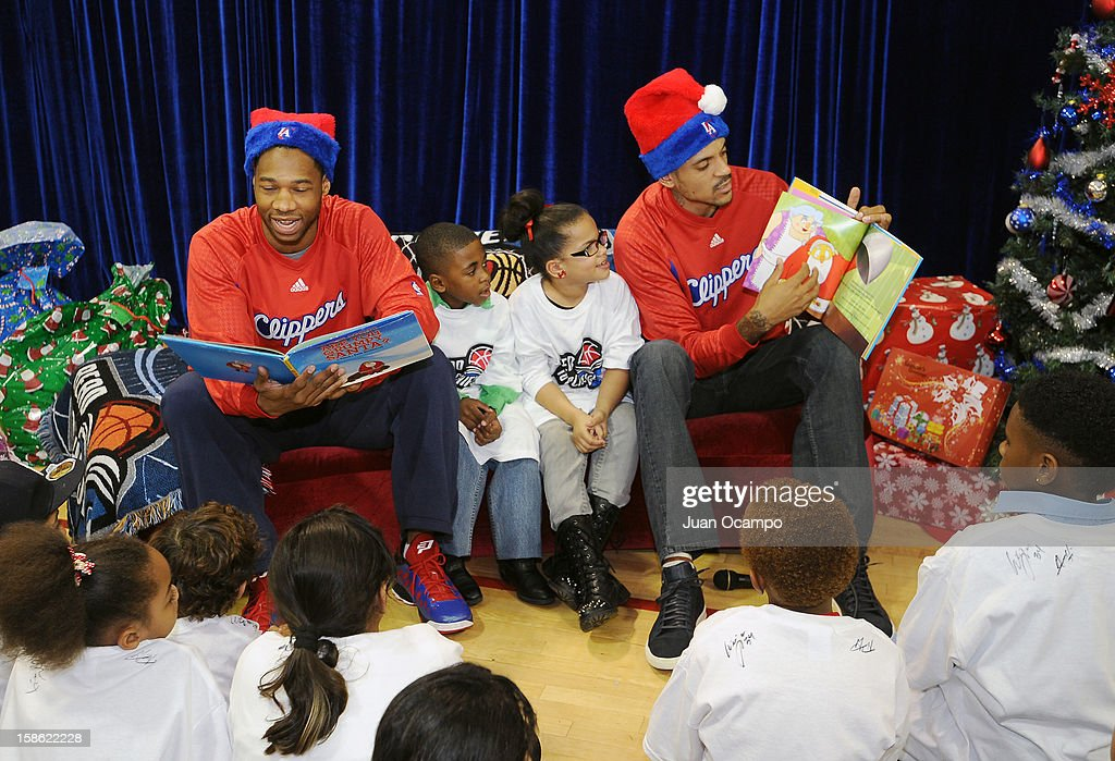 Willie Green #34 and Matt Barnes #22 of the Los Angeles Clippers read to the kids during the Clippers' 'Season of Giving' Adopt a Family event on December 20, 2012 at Salvation Army Seimon Family Youth & Community Center in Los Angeles, California.