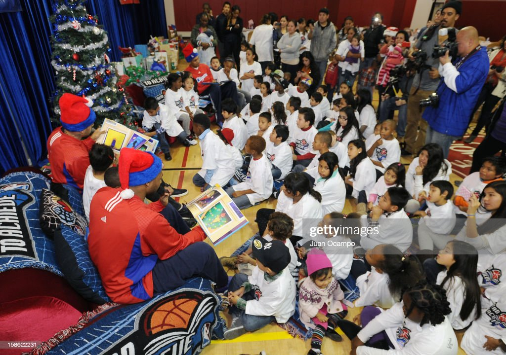 Willie Green #34, Matt Barnes #22 and Grant Hill #33 of the Los Angeles Clippers read to the kids during the Clippers' 'Season of Giving' Adopt a Family event on December 20, 2012 at Salvation Army Seimon Family Youth & Community Center in Los Angeles, California.