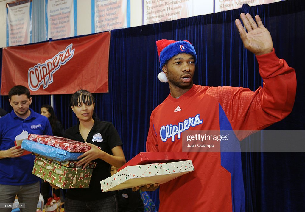 Willie Green #34 of the Los Angeles Clippers helps hand out presents to the families during the Clippers' 'Season of Giving' Adopt a Family event on December 20, 2012 at Salvation Army Seimon Family Youth & Community Center in Los Angeles, California.