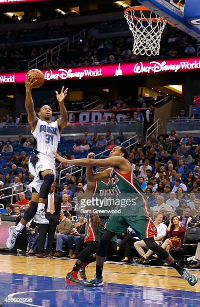 Willie Green of the Orlando Magic attempts a shot over John Henson of the Milwaukee Bucks during the game at Amway Center on November 14 2014 in...