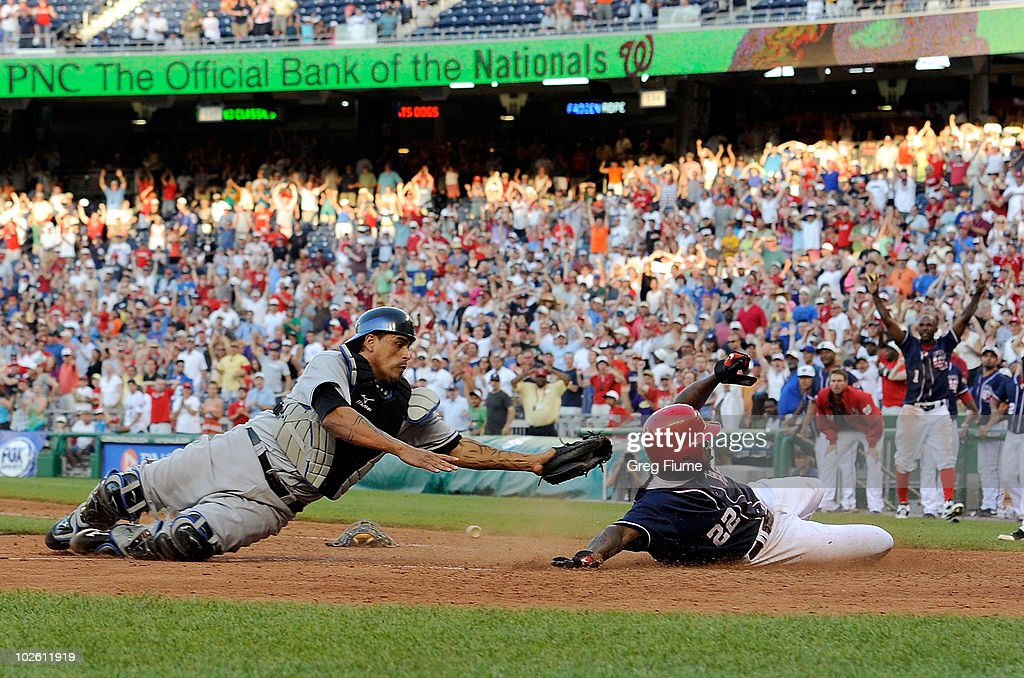 <a gi-track='captionPersonalityLinkClicked' href=/galleries/search?phrase=Willie+Harris&family=editorial&specificpeople=213105 ng-click='$event.stopPropagation()'>Willie Harris</a> #22 of the Washington Nationals ties the game in the ninth inning ahead of the tag of <a gi-track='captionPersonalityLinkClicked' href=/galleries/search?phrase=Henry+Blanco&family=editorial&specificpeople=211366 ng-click='$event.stopPropagation()'>Henry Blanco</a> #4 of the New York Mets at Nationals Park on July 3, 2010 in Washington, DC.