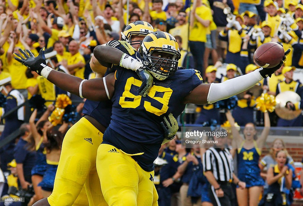 Willie Henry of the Michigan Wolverines celebrates a second quarter interception for a touchdown with Mario Ojemudia and Brennen Beyer while playing...