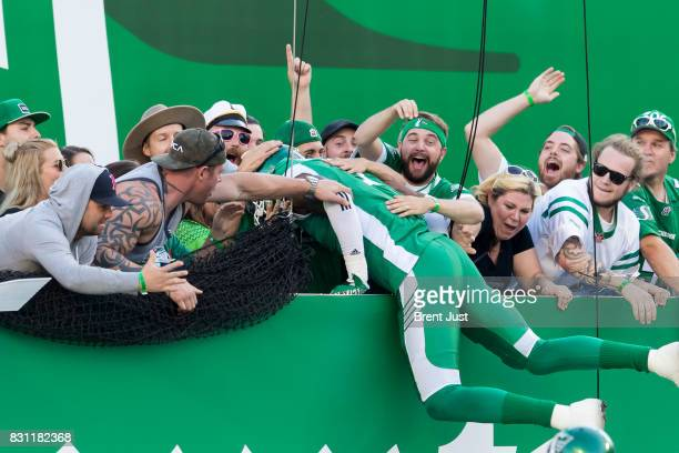 Willie Jefferson of the Saskatchewan Roughriders leaps into the crowd after Ed Gainey of the Saskatchewan Roughriders ran an interception back for a...