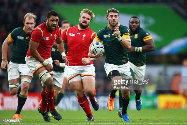 Willie Le Roux of South Africa makes a break from Taulupe Faletau of Wales during the 2015 Rugby World Cup Quarter Final match between South Africa...