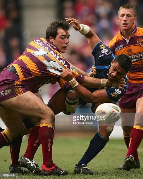 Willie Manu of Hull is tackled by John Skandalis as Keith Mason looks on during the Engage Super League match between Huddersfield Giants and Hull FC...