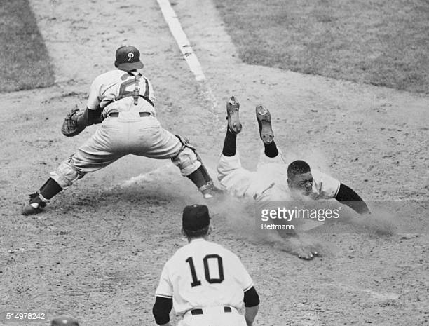 Willie Mays of the New York Giants slides safely into the plate on Wes Westrum's basesfull single in the sixth inning of the game with the...