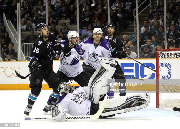 Willie Mitchell and Michal Handzus of the Los Angeles Kings and Devin Setoguchi and Joe Thornton of the San Jose Sharks look on against the San Jose...