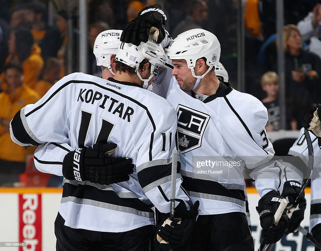 Willie Mitchell #33 celebrates with Anze Kopitar #11 of the Los Angeles Kings on Kopitar's game-winning shootout goal against the Nashville Predators at Bridgestone Arena on October 17, 2013 in Nashville, Tennessee.