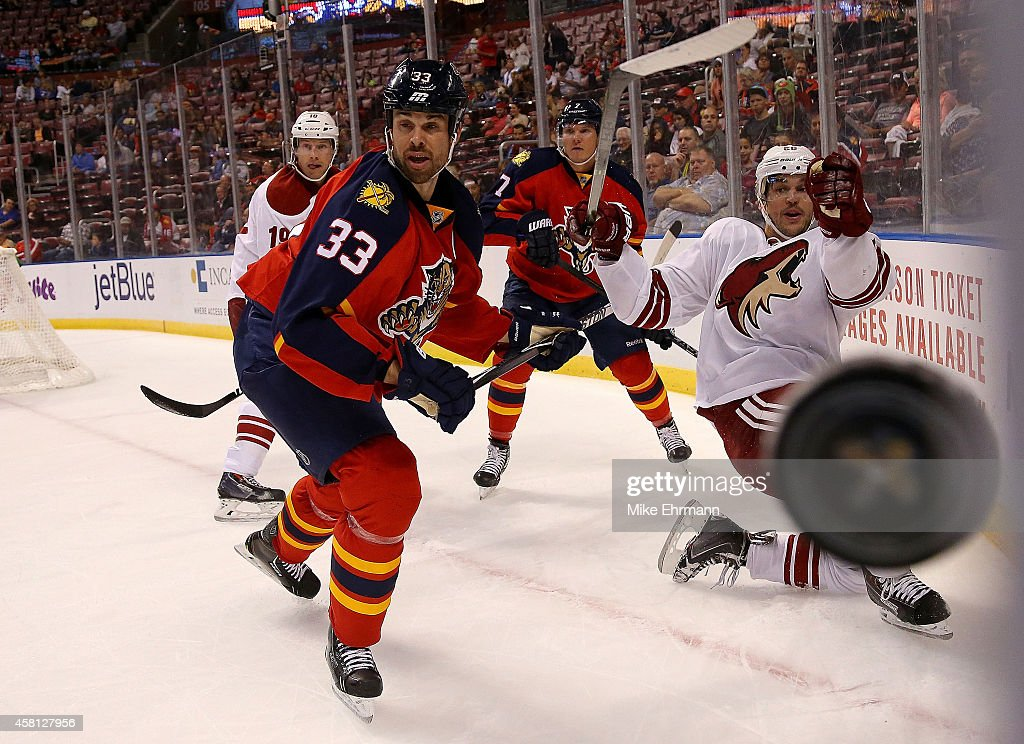 Willie Mitchell of the Florida Panthers and Antoine Vermette of the Arizona Coyotes fight for the puck during a game at BBT Center on October 30 2014...