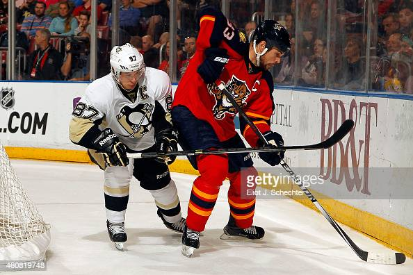 Willie Mitchell of the Florida Panthers digs the puck out from the boards against Sidney Crosby of the Pittsburgh Penguins at the BBT Center on...