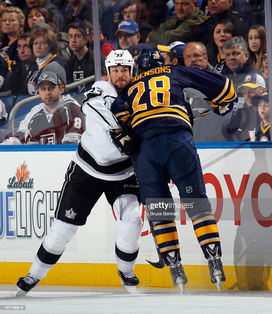 Willie Mitchell #33 of the Los Angeles Kings holds up Zemgus Girgensons #28 of the Buffalo Sabres during the first period at the First Niagara Center on November 12, 2013 in Buffalo, New York.