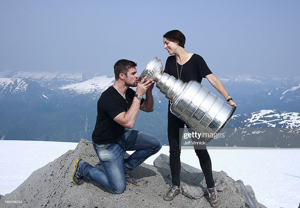 Willie Mitchell #33 of the Los Angeles Kings is given a drink of champagne by his wife Megan from the Stanley Cup at the top of Mount Benedict August 12, 2012 near Port McNeill, British Columbia, Canada. Mitchell took the Stanley Cup to his hometown of Port McNeill, B.C. for his one-day celebration with the prized trophy.