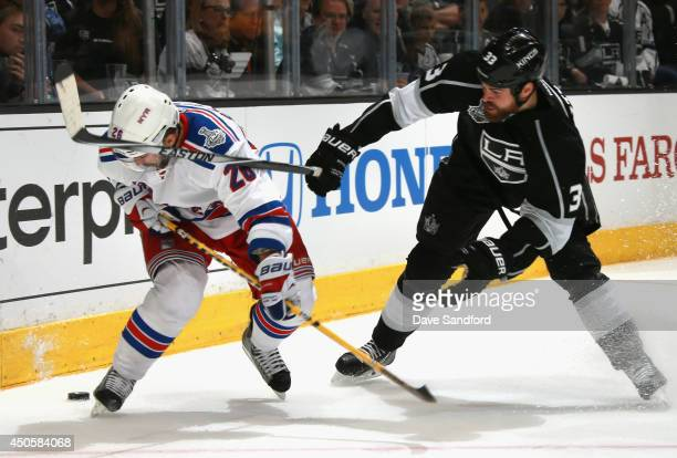 Willie Mitchell of the Los Angeles Kings tries to stop Martin St Louis of the New York Rangers with his stick in the third period of Game Five of the...
