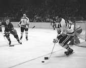 Willie O'Ree of the Boston Bruins skates with the puck as Camille Henry of the New York Rangers looks defend during their NHL game circa 1961 at the...