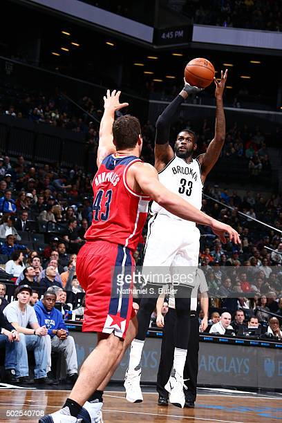 Willie Reed of the Brooklyn Nets shoots against Kris Humphries of the Washington Wizards during the game on December 26 2015 at Barclays Center in...