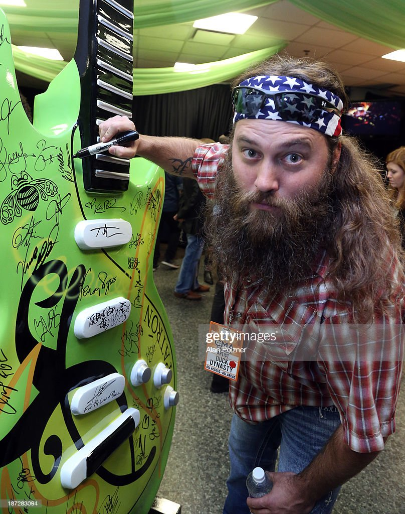 Willie Robertson of Duck Dynasty signs a giant Patron tequila guitar backstage at the CMA Awards to benefit the 'Keep the Music Playing' music education on November 3, 2013 in Nashville, Tennessee.
