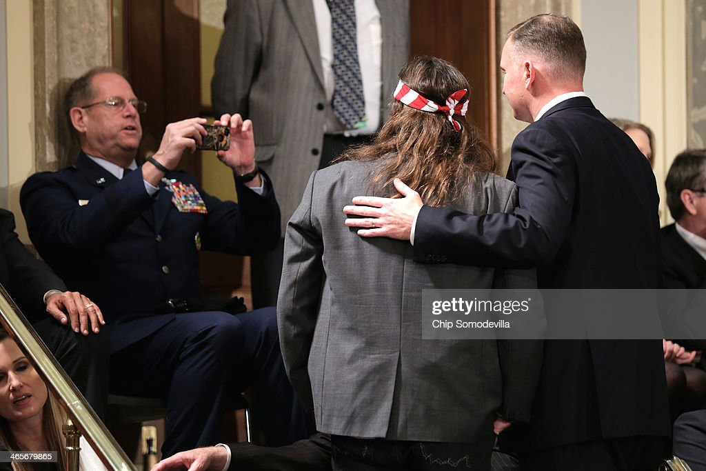 Willie Robertson (C) of the television show Duck Dynasty poses for a photo as he waits for U.S. President Barack Obama to deliver the State of the Union address to a joint session of Congress in the House Chamber at the U.S. Capitol on January 28, 2014 in Washington, DC. In his fifth State of the Union address, Obama is expected to emphasize on healthcare, economic fairness and new initiatives designed to stimulate the U.S. economy with bipartisan cooperation.