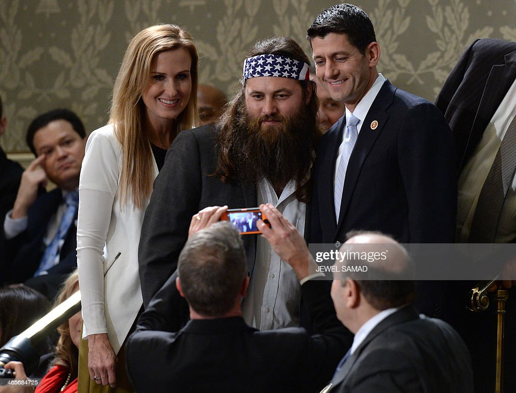 Willie Robertson (C) of the television show Duck Dynasty poses for a picture with US Repubklican Representative from Wisconsin Paul Ryan (R) and his wife Janna Ryan before US President Barack Obama delivers his State of the Union address before a joint session of Congress on January 28, 2014 at the US Capitol in Washington. AFP PHOTO/Jewel Samad