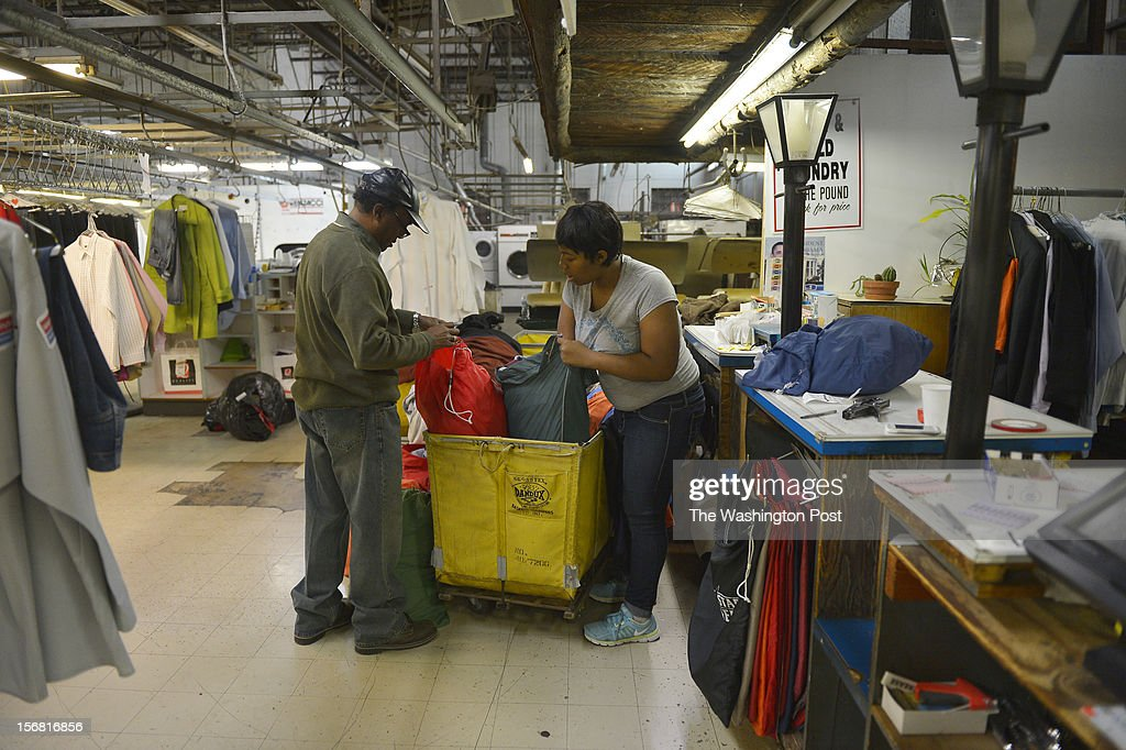 Willie Thomas Craft, Jr., and employee Kierria Johnson, sort through bins of laundry at the Dean Ave. Cleaners on November 20, 2012 in Washington, D.C. Willie Craft, 82, bought the cleaners in 1978 which has pretty much remained the same ever since. He's got a steady stream of return customers and folks who just drop by to visit. Willie's son, Willie Thomas Craft, Jr. also works there at the cleaners preparing to take over the business from his father when he retires.