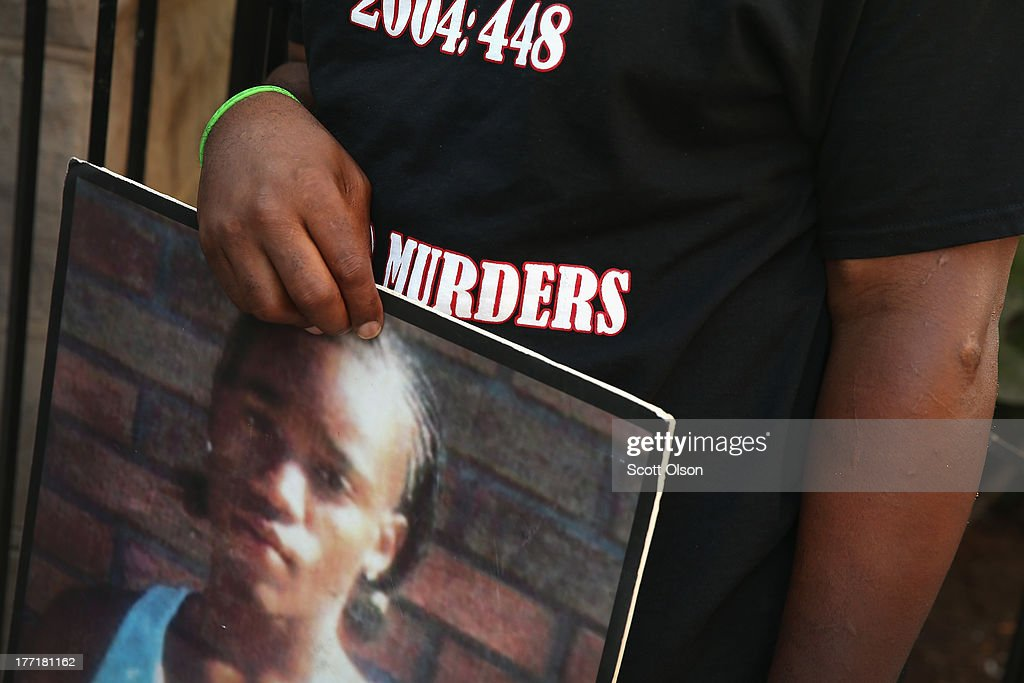 Willie Williams Jr. holds a picture of his son Wille Williams III during a prayer vigil outside the Uptown Baptist Church for the people wounded in Monday's shooting on August 21, 2013 in Chicago, Illinois. Five people who were standing in front of the church were shot August 19, when a gunman opened fire from a passing vehicle. Williams III was 17-years-old when he was murdered in 2006.